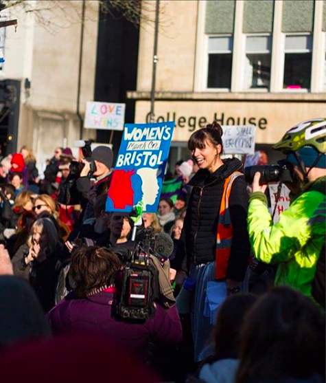 A womens march with carly Wilkinson holding a sign at the centre