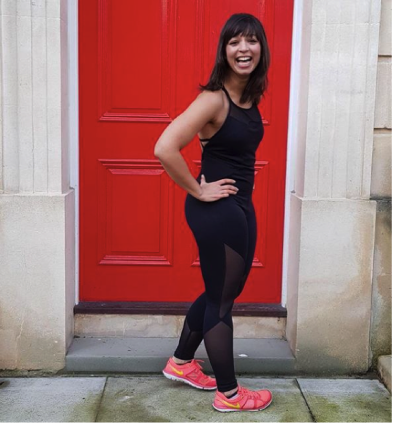 A woman in fitness gear stands smiling in front of a red door