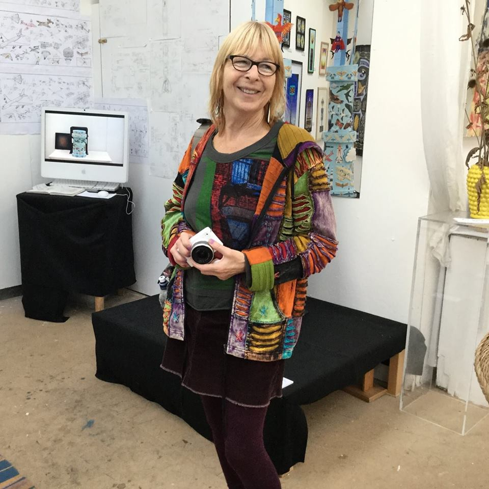 A full length photograph of a women with a colourful patchwork top. She smiles and holds a camera