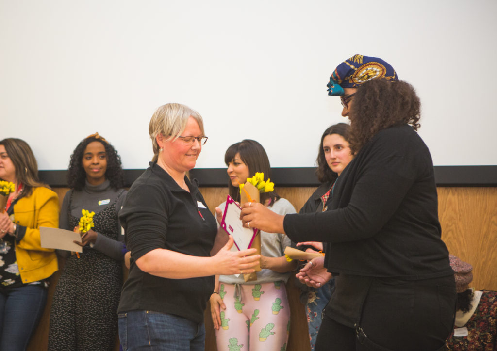 Hedi Simpson is handed a bunch of daffodils and a certificate.