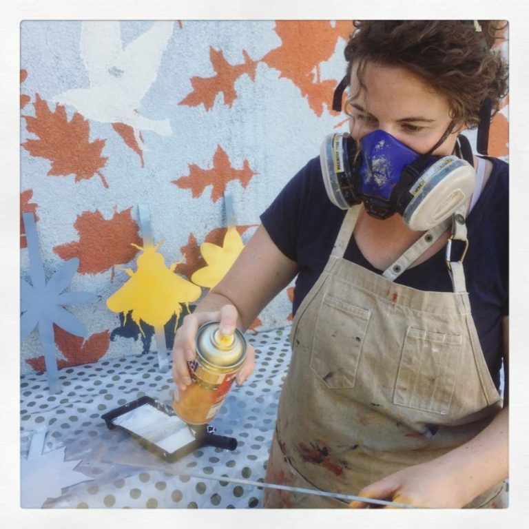 Becky wears a dust mask and uses a spray can