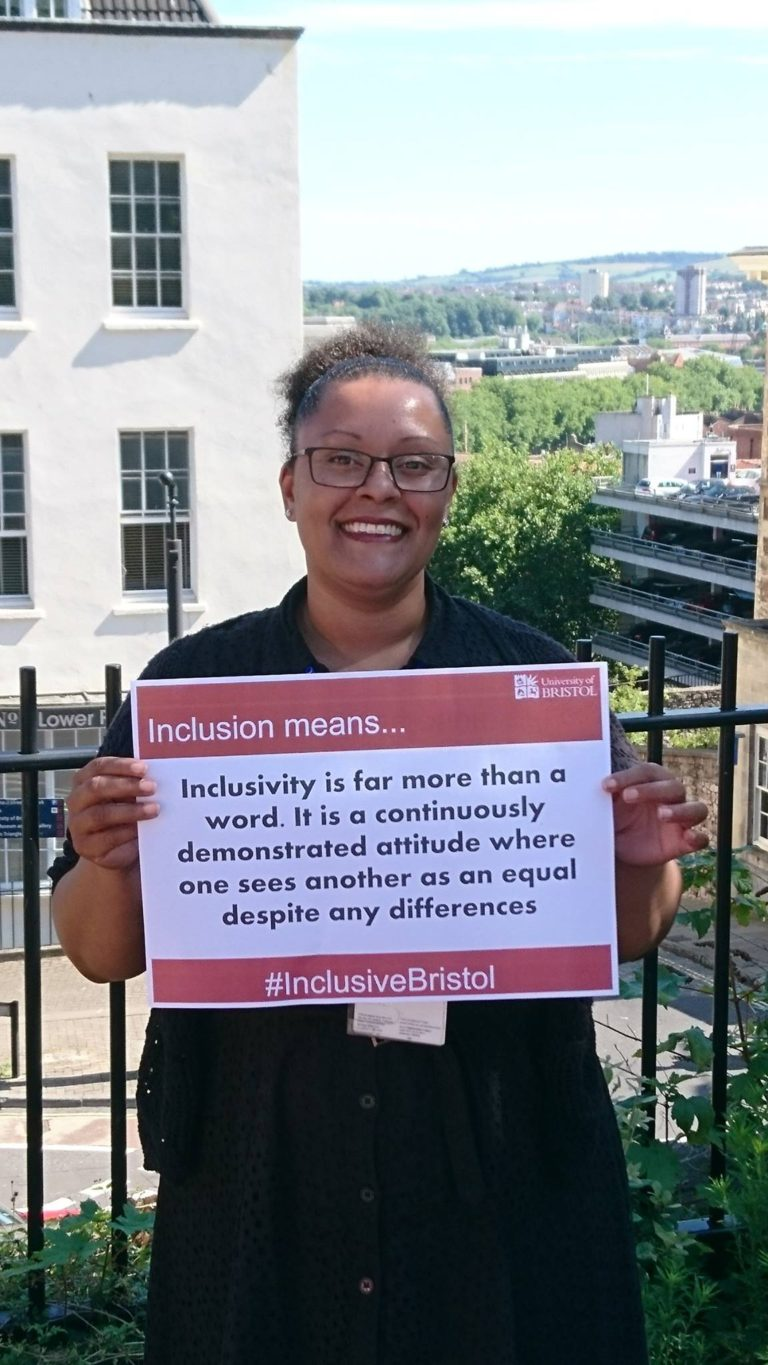 A mixed race woman holds up a sign which reads: Inclusivity is far more than a word. It is a continuously demonstrated attitude where one sees another as equal despite any differences. She is smiling, it is sunny and you can see across the top of Bristol in the background