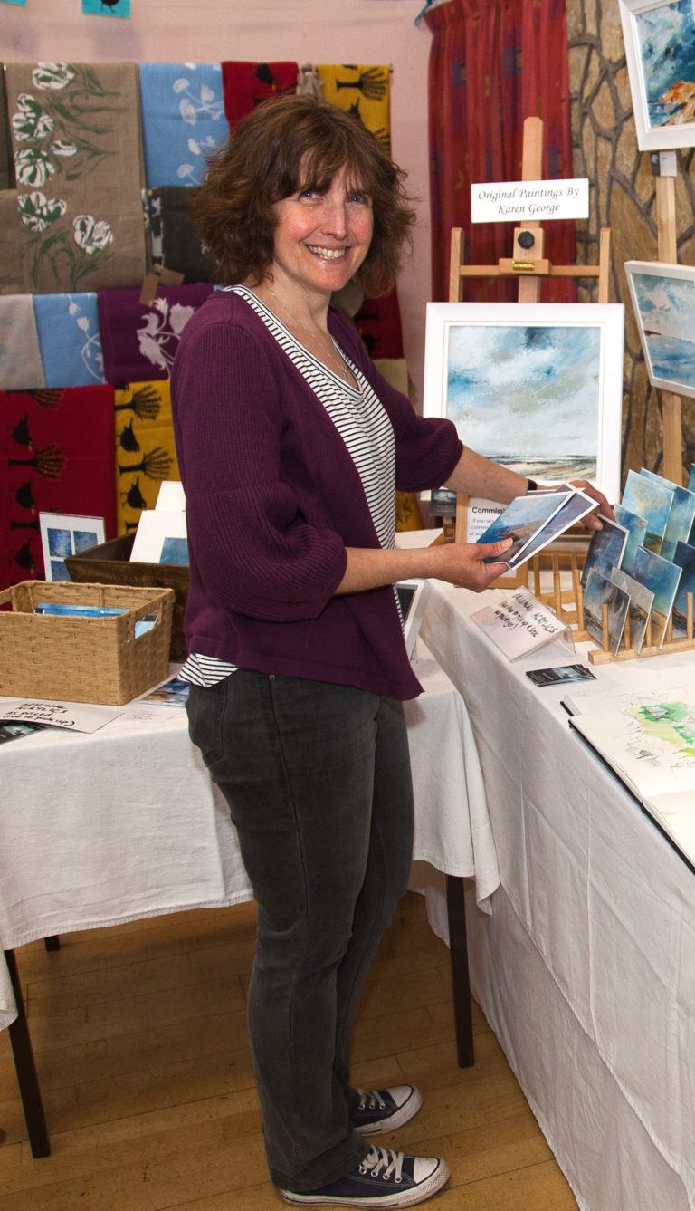 A woman stands in front of an art stall holding two postcards. The stall has paintings of the sea.