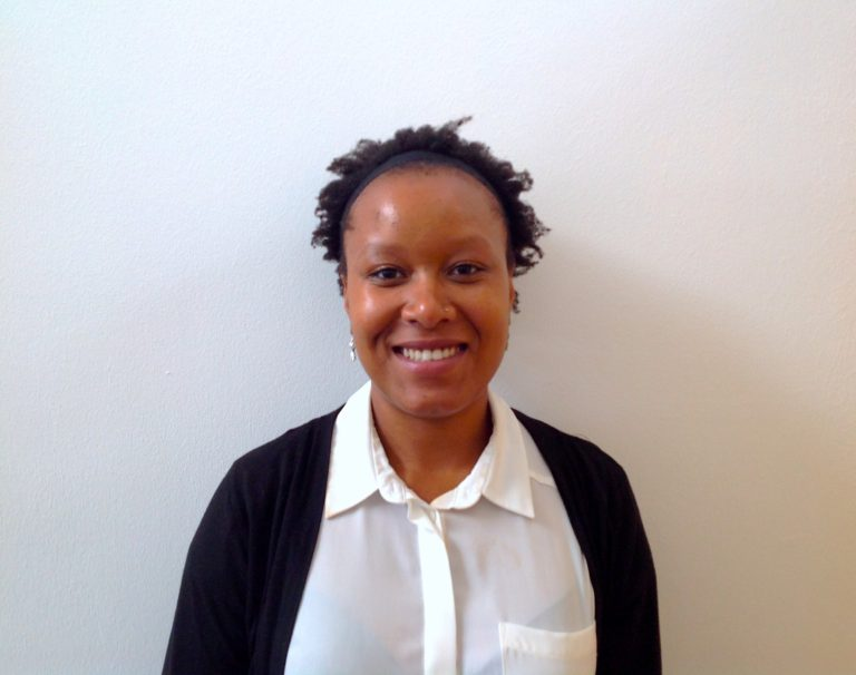 A woman wearing a white shirt and black cardigan stands with her back against a white wall. She has short black hair and smiles at the camera